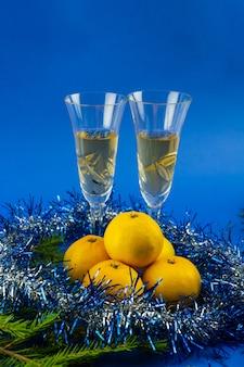 Des guirlandes bleues sur fond bleu enveloppent des mandarines et remplissent des verres de vin.