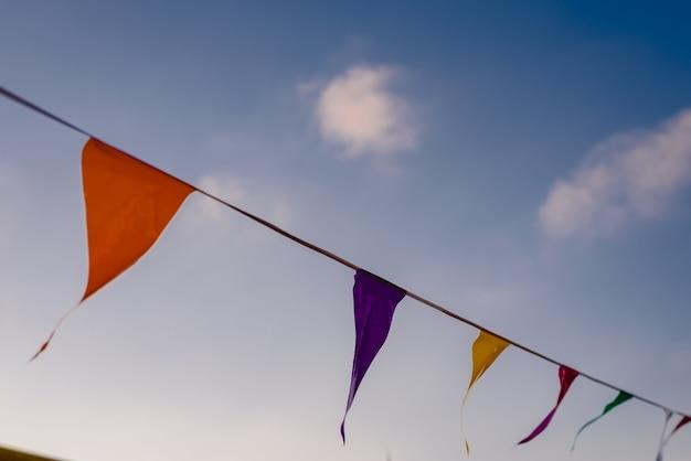 Des guirlandes colorées ondulant dans le vent sur un ciel bleu idéal pour décorer un anniversaire.