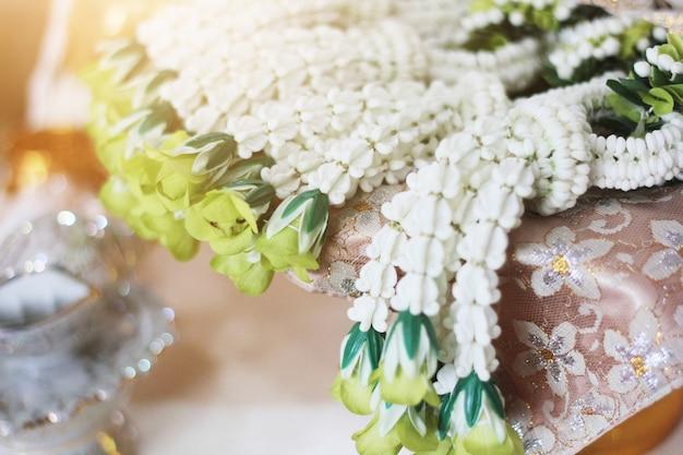 Des guirlandes de fleurs sur un plateau en or lors de la cérémonie du mariage thaïlandais traditionnel. guirlande de jasmin