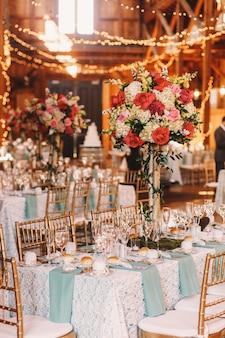 Guirlandes de lumière jaune pendre sur les tables à manger décorées