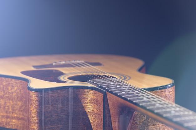 Guitare acoustique avec un beau bois sur fond noir à la lumière d'un projecteur.