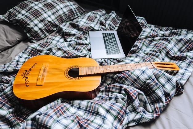 Guitare acoustique en bois sur le lit avec ordinateur portable.
