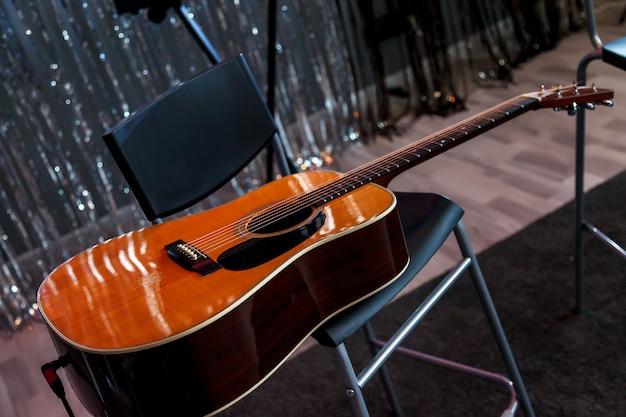 Guitare acoustique sur fauteuil en plastique à l'intérieur d'un studio contemporain. la guitare acoustique se trouve sur le noir devant le fond brillant de mur de guirlande. temps pour le passe-temps et les loisirs. espace de copie pour le site