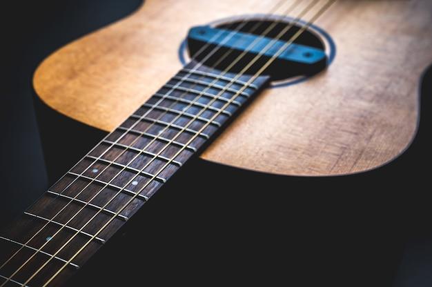 Guitare acoustique, instrument de musique reposant contre un mur noir foncé avec espace copie, gros plan d'une guitare classique en bois