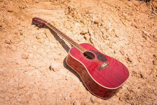 Guitare acoustique se trouvant sur une terre déserte