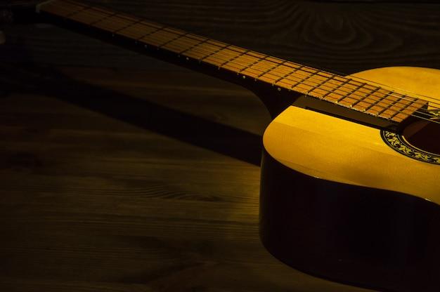 Guitare acoustique sur une table en bois éclairée par un rayon de lumière.