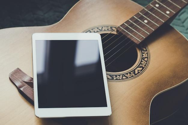 Guitare acoustique et tablette numérique sur un canapé