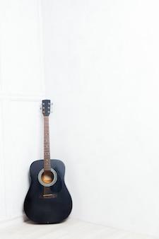 Guitare calée devant un mur blanc