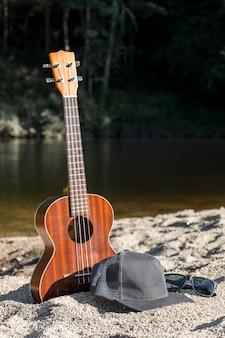 Guitare avec capuchon et lunettes de soleil sur le rivage près de la surface de l'eau