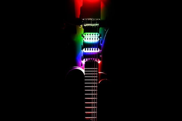 Guitare électrique blanche dans les lumières de l'arc-en-ciel. manche et touche d'instrument de musique. photo de style créatif avec des ombres.