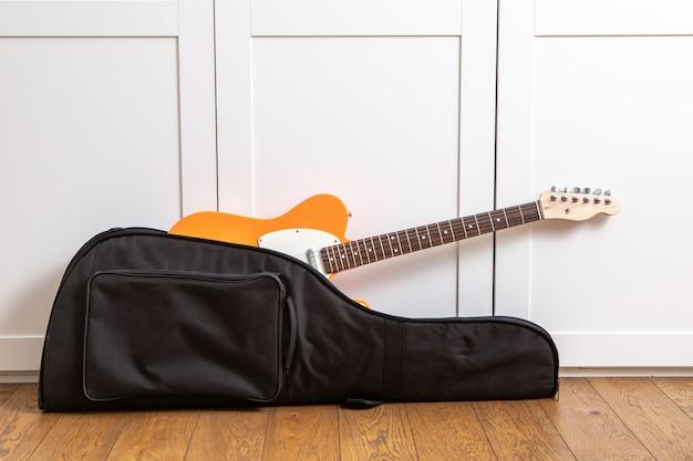 Guitare électrique dans le boîtier près d'un mur blanc dans la chambre