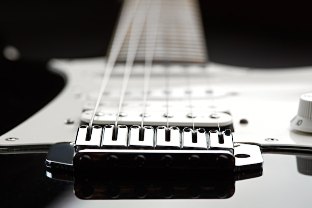 Guitare électrique, mise au point sur les cordes, dessus noir sur fond, personne
