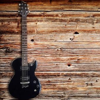 Guitare électrique noire sur fond de bois