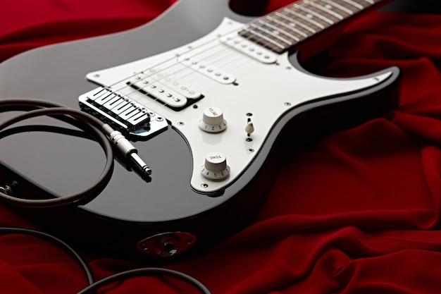 Guitare électrique noire, fond rouge, personne