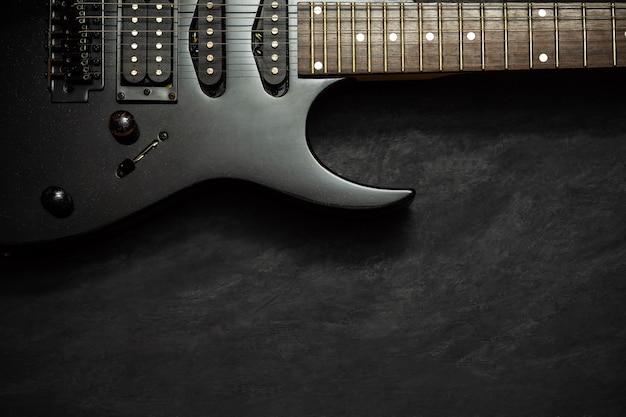 Guitare électrique noire sur sol en ciment noir.