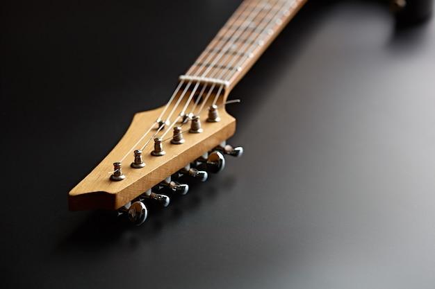 Guitare électrique, vue rapprochée sur la tête, fond noir, personne