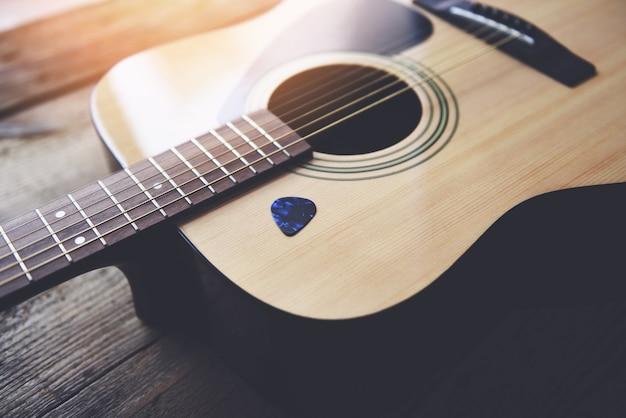 Guitare reposant sur le vieux fond en bois, close up guitare acoustique et médiator