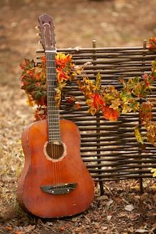 Une guitare se tient près d'une clôture en osier entrelacée de feuilles d'automne