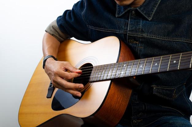 Guitariste acoustique tient la guitare. et jouer de la guitare concepts de loisirs et de détente en temps libre pour une bonne qualité de vie