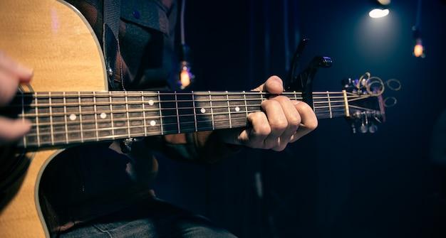 Le guitariste joue de la guitare acoustique avec capodastre
