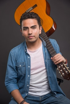 Guitariste posant avec guitare sur fond sombre.