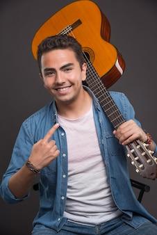 Guitariste posant avec guitare et se pointant sur fond sombre.