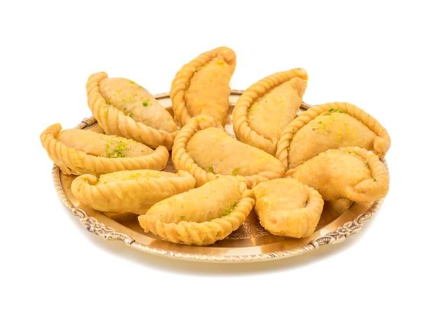 Gujia est un aliment sucré indien sur fond blanc