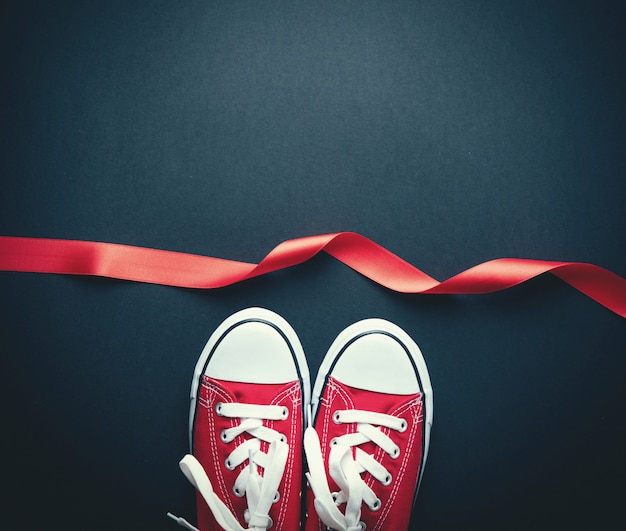 Gumshoes rouges avec des lacets blancs et ruban rouge