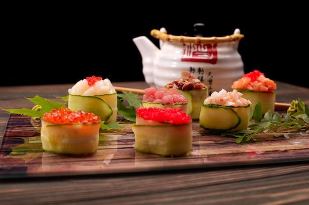 Gunkan maki au concombre, avec caviar, thon. pétoncle, anguille, crevette, anguille et saumon, sur une planche de bois, avec des feuilles d'érable et d'acacia