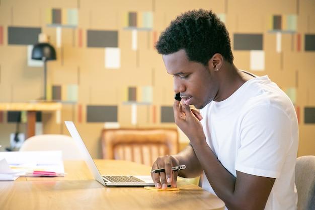 Guy afro-américain en t-shirt blanc parler sur cellule, assis à table avec ordinateur portable et plans et notes d'écriture