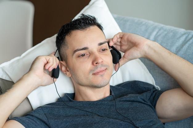Guy aime la musique allongé sur le canapé avec des écouteurs