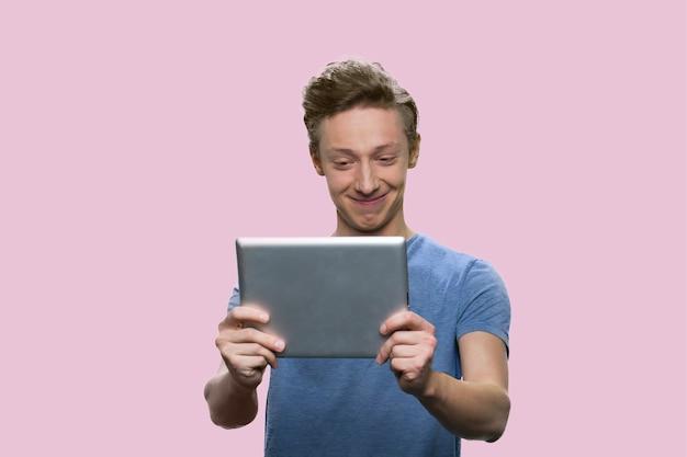 Guy américain souriant en regardant la tablette. écolier caucasien isolé sur fond rose.