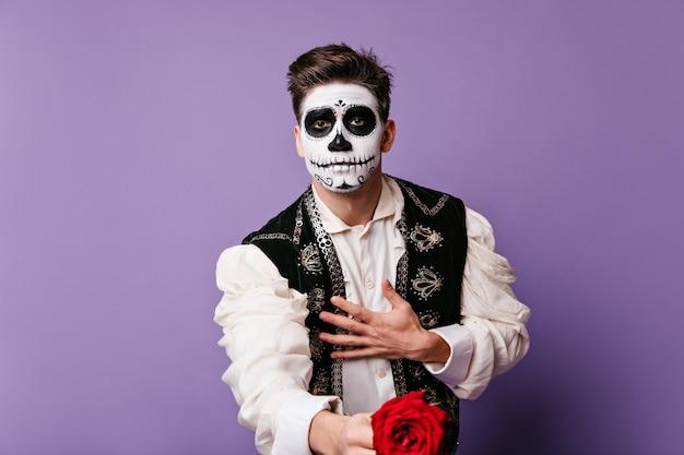 Guy amoureux de l'art du visage donne une belle rose, posant pour un portrait dans un mur lilas.