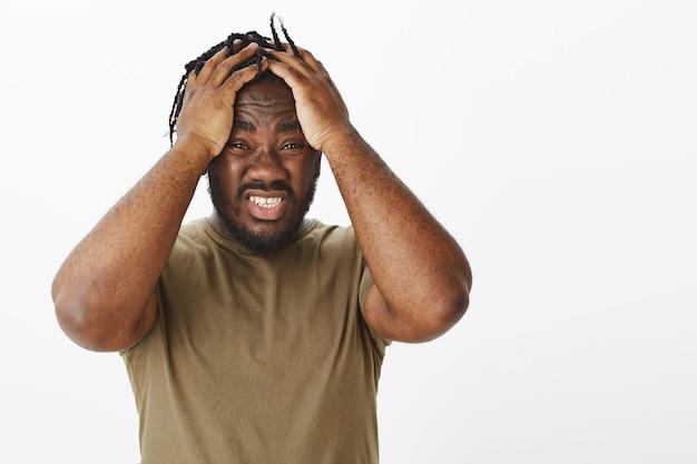 Guy anxieux dans un t-shirt marron posant contre le mur blanc