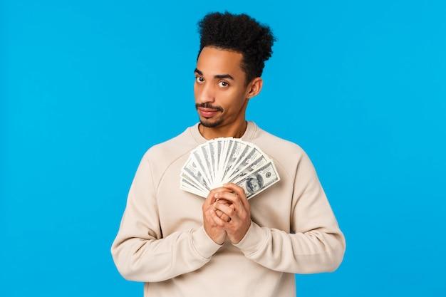 Guy a de l'argent, pensant à quoi acheter, comment gaspiller de l'argent pendant la saison des soldes