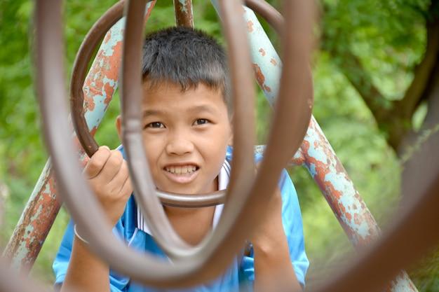 Guy asiatique jouant sur le terrain de jeu avec bonheur en vacances