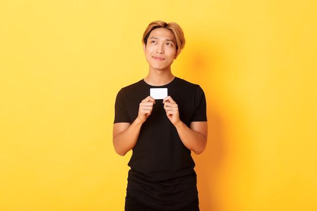 Guy asiatique souriant réfléchi pensant tout en montrant la carte de crédit, à la recherche du coin supérieur gauche rêveur, mur jaune