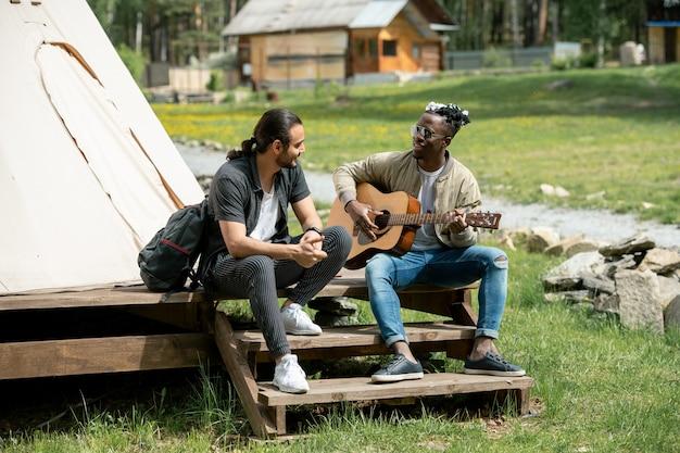 Guy assis sur l'étape et jouant de la guitare pour un ami pendant qu'ils passent du temps au festival de la campagne