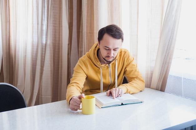 Guy assis près de la fenêtre à la table et lit