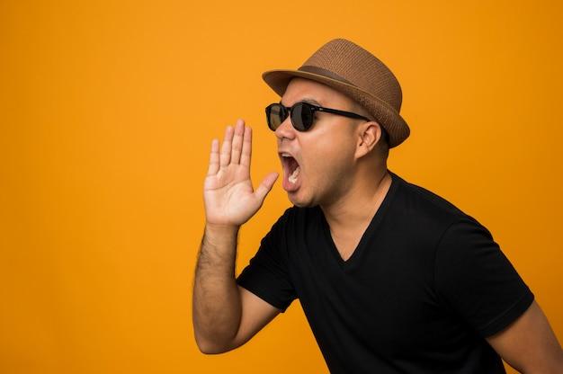Guy au chapeau portant des vêtements décontractés mis sur des lunettes de soleil en criant avec les mains en coupe autour de la bouche