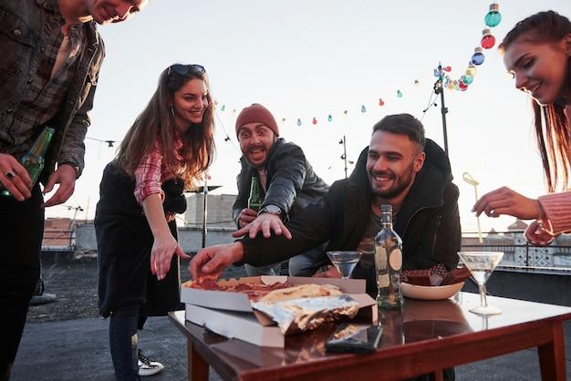 Guy au chapeau rouge fait un visage affamé et essaie d'atteindre ce produit frais. manger de la pizza à la fête sur le toit. les bons amis ont le week-end avec de la nourriture délicieuse et de l'alcool