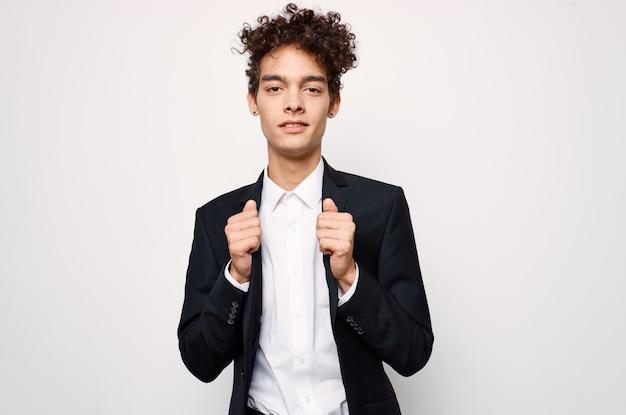 Guy aux cheveux bouclés dans un style moderne de blazer noir de mode costume. photo de haute qualité