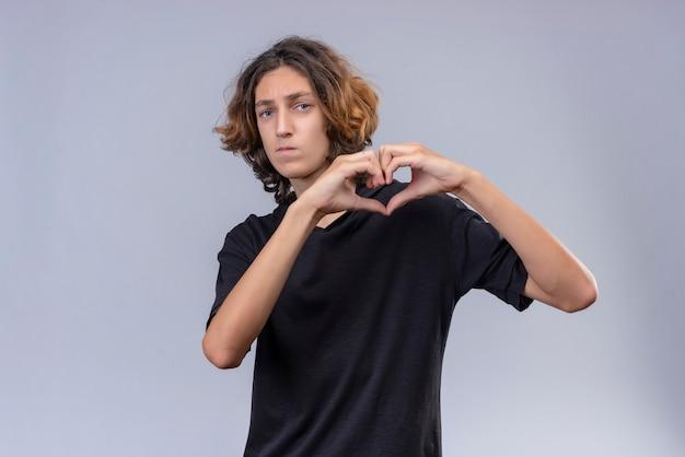 Guy aux cheveux longs en t-shirt noir montre le cœur avec les mains sur le mur blanc
