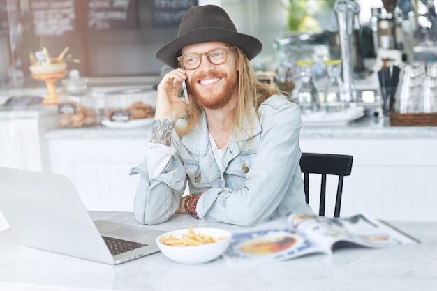 Guy aux cheveux longs, vêtu d'une veste en jean à la mode et d'un chapeau noir au café