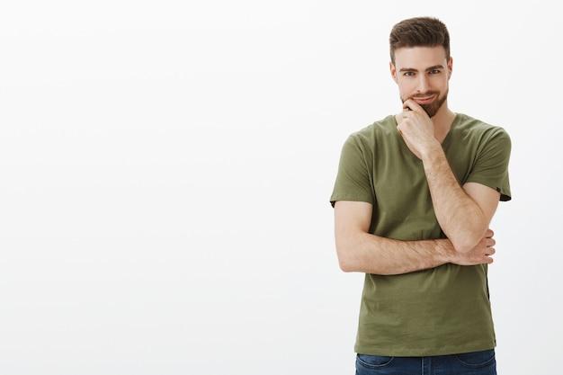 Guy ayant un excellent plan, intrigant quelque chose de grand et de mal, souriant comme un génie et se frottant la barbe, ayant quelque chose de méchant à l'esprit, posant ravi sur un mur blanc