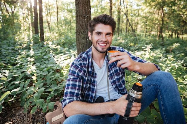 Guy buvant du thé en forêt