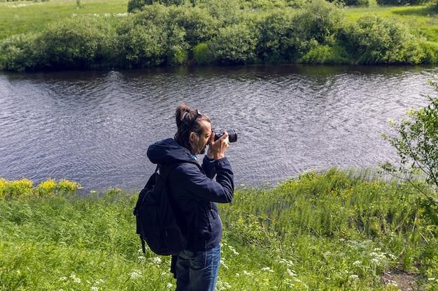 Guy ca sac à dos et lunettes noires se tient en arrière et prend des photos du champ sur la caméra