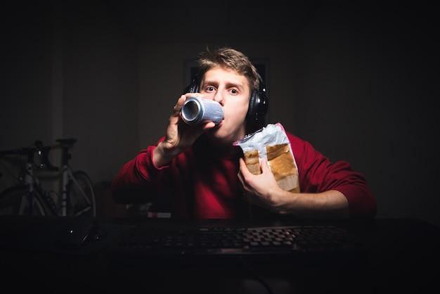 Guy avec un casque tient des collations dans sa main et regarde l'écran de l'ordinateur