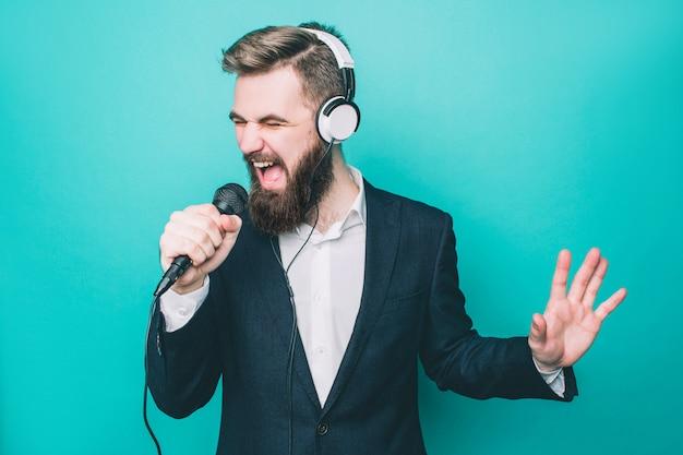 Guy chante avec un microphone et porte des écouteurs