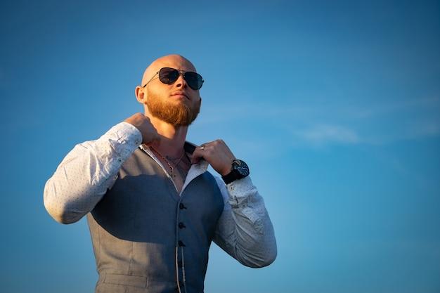 Guy chauve avec une barbe élégante et des lunettes de soleil sur une surface du ciel au coucher du soleil